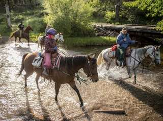 Horseback riders go through a river at the