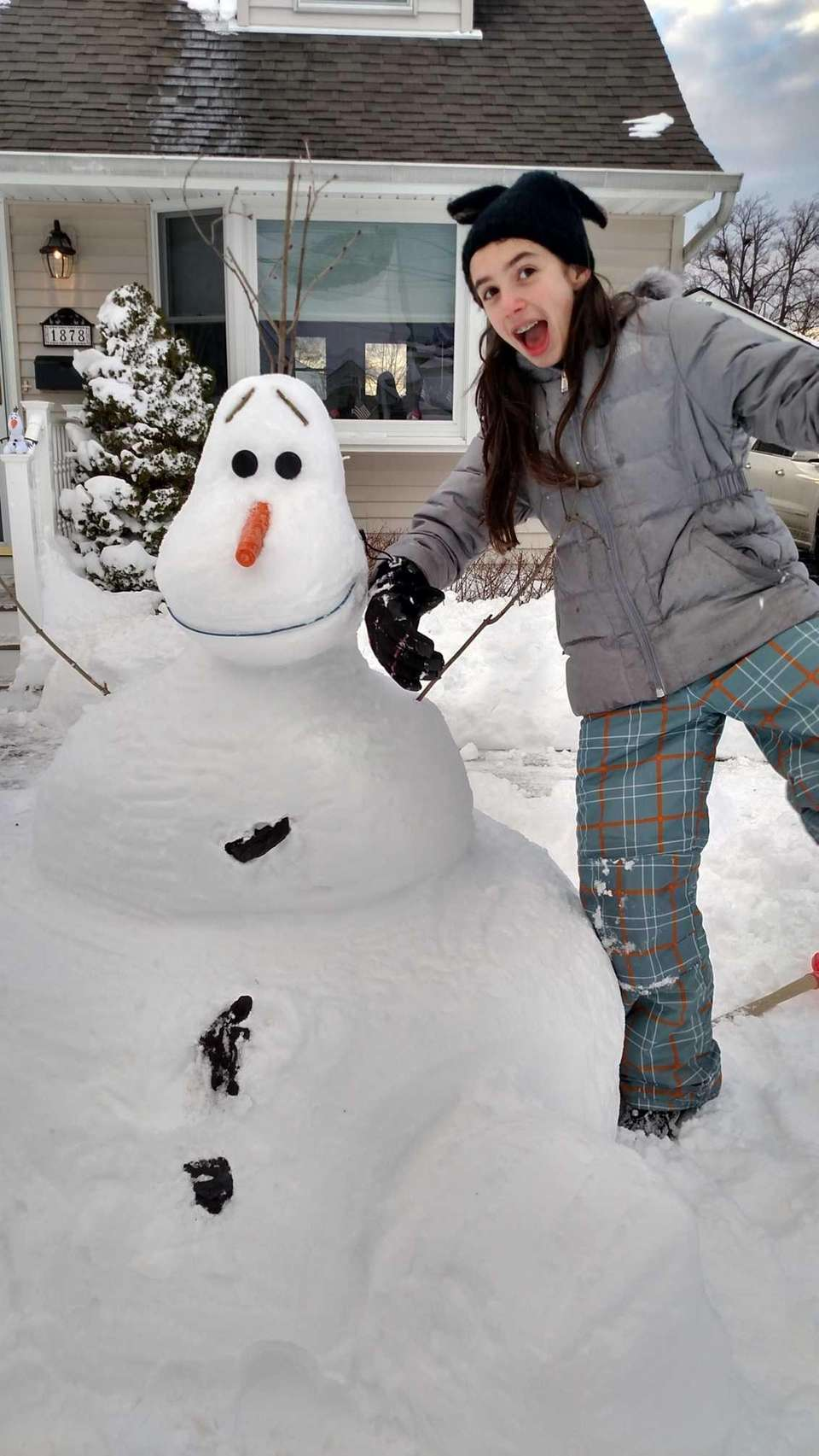 Abby Maiello with her snowman in North Bellmore.