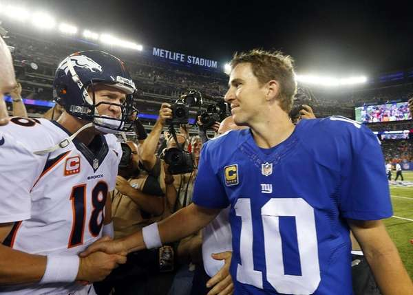 Peyton Manning, left, of the Denver Broncos shakes