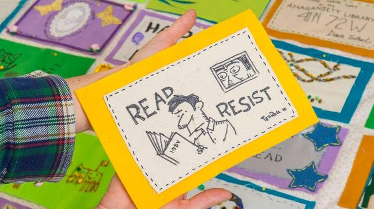 Children's Librarian Evan Harris holds a quilt panel