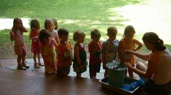 Toddlers watch a counselor make home-made ice cream