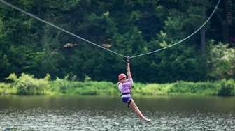 A girl rides the zip line at Camp