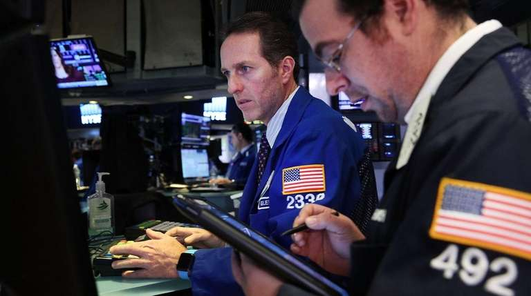 Traders work on the floor of the