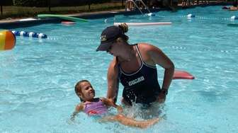 A counselor teaches a young camper some of