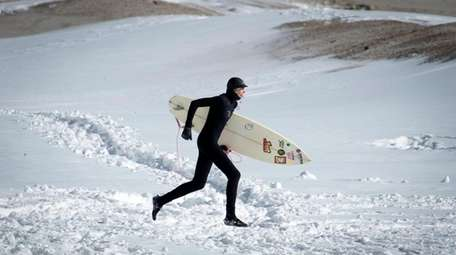 A surfer runs along the snow-covered sand in