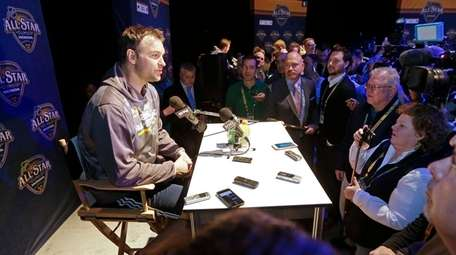 John Scott, left, answers questions during NHL All-Star