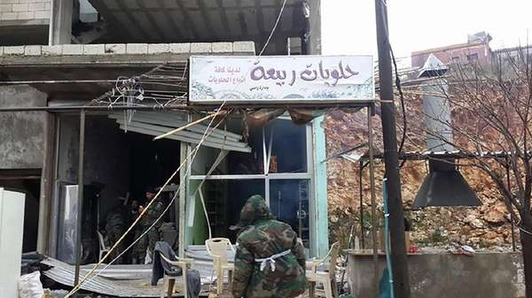 Syrian pro-government forces inspect a building in the