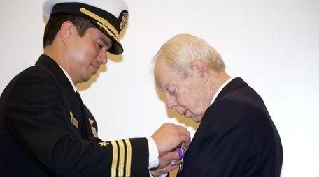 U.S. Navy Cmdr. Dom Pastorin, left, presents World