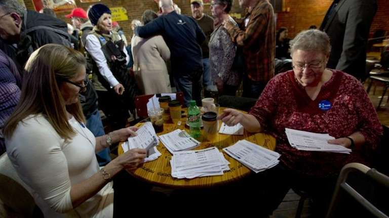 Volunteers sort through commitment cards to caucus for