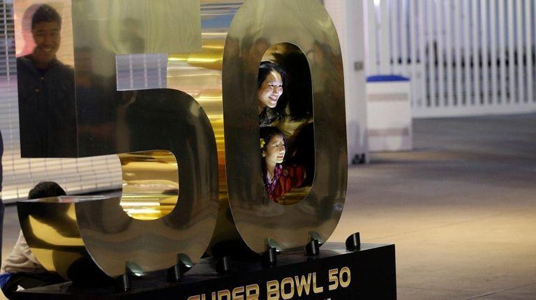 Visitors pose for photos around a Super