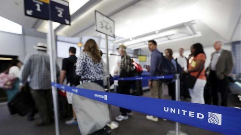Groups of passengers wait at a United Airlines