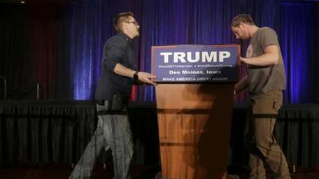 Workers takes the podium down after Republican presidential