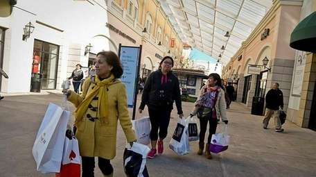 Shoppers walk with their bags in hand