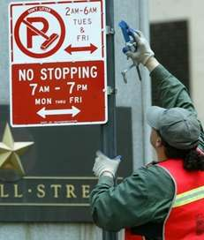 A man changes the parking rule sign to