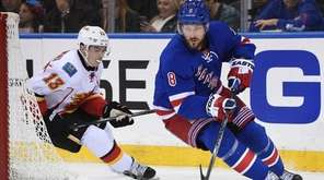 Rangers' Kevin Klein skates for the puck ahead