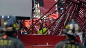 Workers begin the process of disassembling a crane