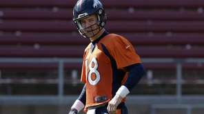 Denver Broncos quarterback Peyton Manning stands on the