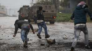 Palestinian protesters throw stones at Israeli military vehicles