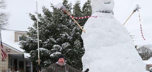 Mike Fregoe stands beside a snowman, over 14-feet