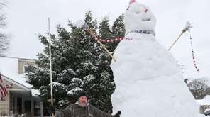 Mike Fregoe stands beside a snowman, over 14-feet