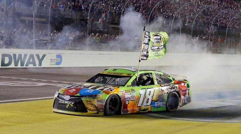 Kyle Busch celebrates after winning the NASCAR