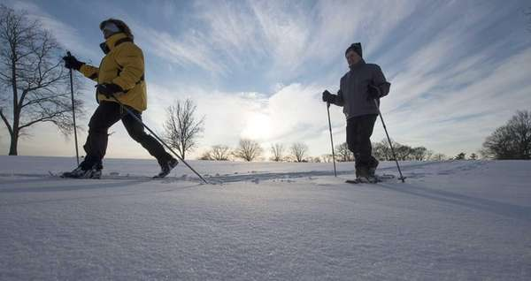 A man and woman traverse a snow-covered Bethpage