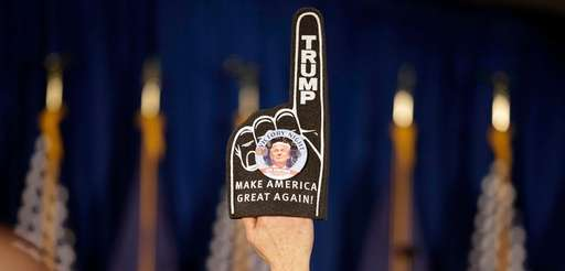 A supporter holds a foam finger sign promoting