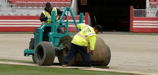 Workers install sod on the field at