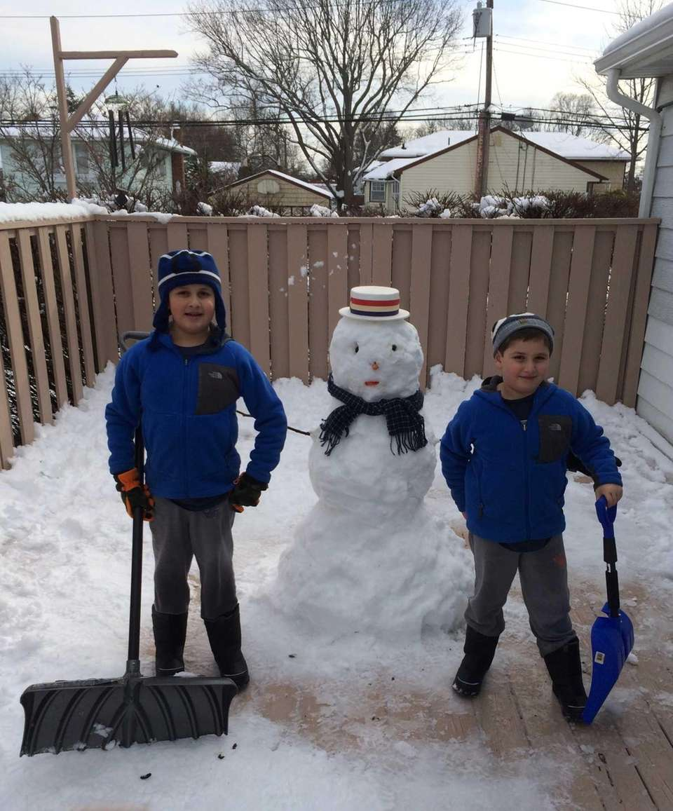 Max and Sam Greenfield building a snowman at