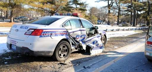 A damaged Suffolk County police car sits on