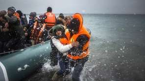 Refugees and migrants disembark on a beach after