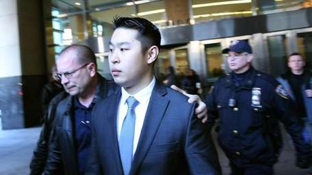 NYPD Officer Peter Liang is escorted out of