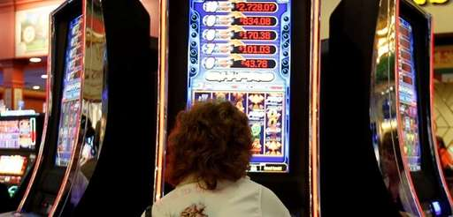 A woman plays a video lottery terminal Oct.