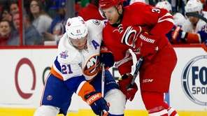 New York Islanders' Kyle Okposo (21) battles with