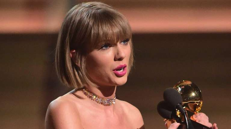Taylor Swift accepts the Grammy for the album
