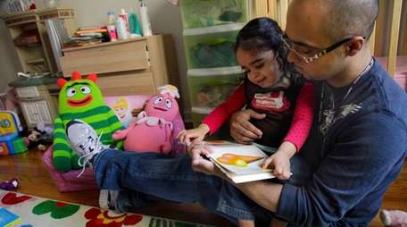 Christopher Astacio reads with his daughter Cristina, 2,