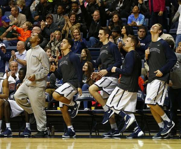 The Monmouth Hawks bench reacts to a