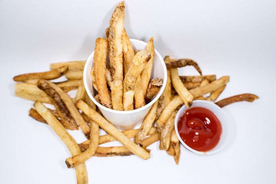 French fries spill from a tall cup of