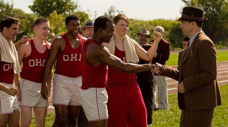 Stephan James, center, as Jesse Owens, and