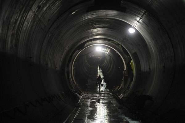 A worker walks in the west tunnel between