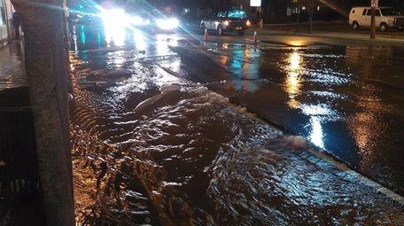 Water from a broken main flows down Merrick