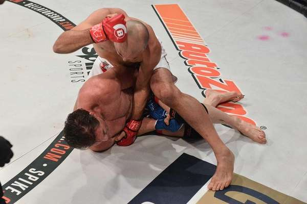 Royce Gracie (top) punches Ken Shamrock at Bellator