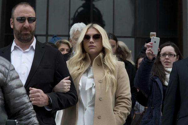 Pop star Kesha, center, leaves Supreme Court in