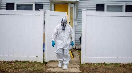 Worker in hazmat suit outside the house on