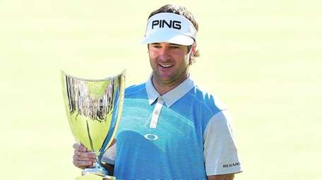 Bubba Watson holds the championship trophy on