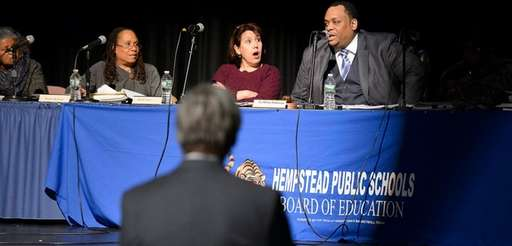 Hempstead school board president LaMont Johnson, right, speaks