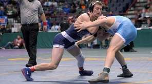 Hauppauge's Chris Mauriello, center, wrestles against Brewster's Grant