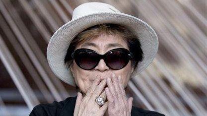 Yoko Ono blows a kiss as she poses
