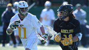 Adelphi midfielder Anthony Gomes is defended by LIU