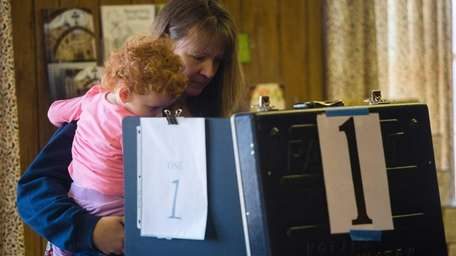 A woman holding her child votes at the
